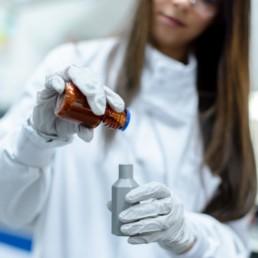 woman in white long sleeve shirt holding orange and white plastic bottle